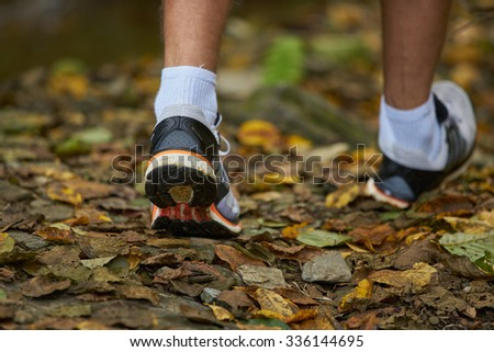 fitness man walking cross in autumn forest