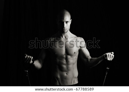 Fitness man with resistance bands, Low key - stock photo