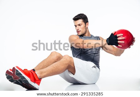 Fitness man working out with fitness ball isolated on a white background - stock photo
