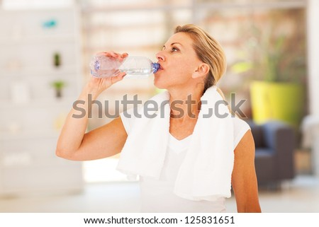 fitness mature woman drinking water after exercise - stock photo