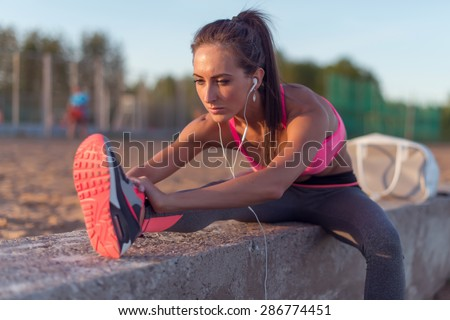 Fitness model athlete girl warm up stretching her hamstrings, leg and back. Young woman exercising with headphones listening music outdoors on beach or sports ground at evening summer. - stock photo