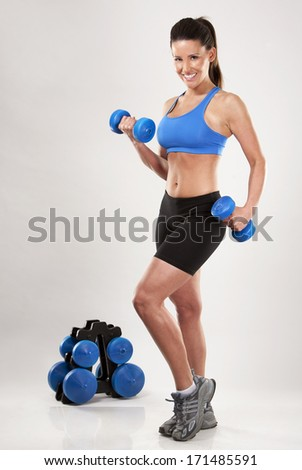 fitness model brunette wearing blue outfit on light background - stock photo