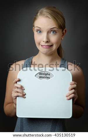 fitness model holding bathroom scales, looking concerned with the words weight worries written on the scales dial - stock photo