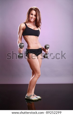 Fitness model's dumbbell routine - stock photo