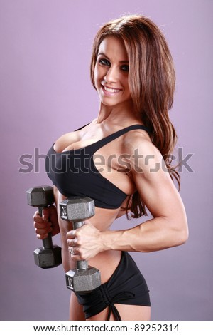 Fitness model's dumbbell routine - stock photo