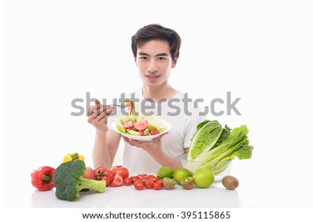 Fitness Model with Fruits and Vegetables-Cheerful young man eating healthy salad, fruits - stock photo