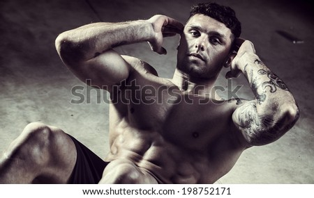 Fitness model with large muscles doing situps  - stock photo