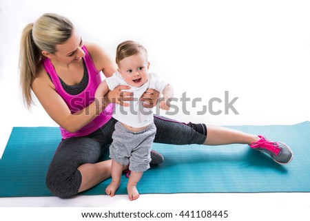 Fitness mother with a baby on the mat - stock photo