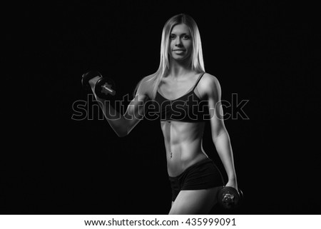 Fitness motivation. Fitness woman with dumbbells on a black background. Perfect female sports figure. Fitness woman posing in the studio. Fitness photo shoot in the studio. Fitness bikini