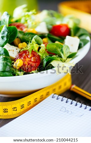 Fitness nutrition diary, salad and measuring tape on rustic wooden table. Mixed greens, tomatoes, diet cheese, olive oil and spices for healthy lifestyle concept. - stock photo