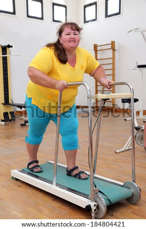 fitness - overweight woman running on trainer treadmill - stock photo
