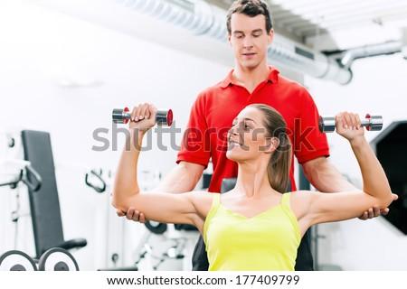 Fitness Paar im Fitnessstudio trainieren mit Gewichten und vergleichen sich - stock photo