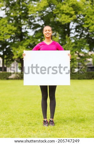 fitness, park, advertising, information and people concept - smiling teenage girl with blank white board outdoors - stock photo