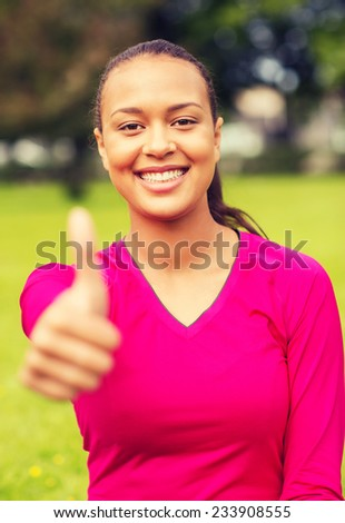 fitness, park, happiness and people concept - portrait of smiling african american woman showing thumbs up outdoors - stock photo