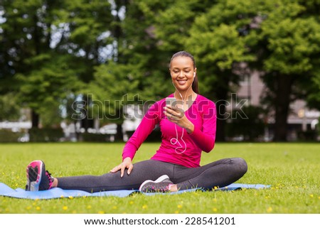 fitness, park, technology and sport concept - smiling african american woman with smartphone and earphones sitting on mat outdoors - stock photo