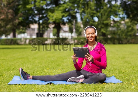 fitness, park, technology and sport concept - smiling african american woman with tablet pc computer and headphones on mat outdoors