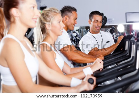 fitness people biking in gym with personal trainer - stock photo