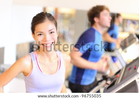 Fitness people portrait in gym. Woman smiling happy during running workout on treadmill in fitness center. Mixed race Cauasian / Chinese Asian female fitness model. - stock photo