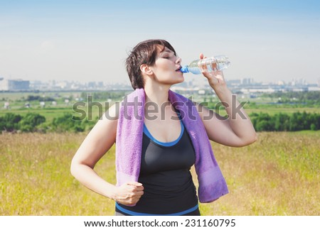 Fitness plus size woman drinking water  - stock photo
