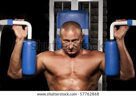 Fitness - powerful muscular man doing weightlifting in gym