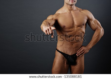 Fitness - powerful muscular man lifting weights / Muscular man with dumbbells on black background