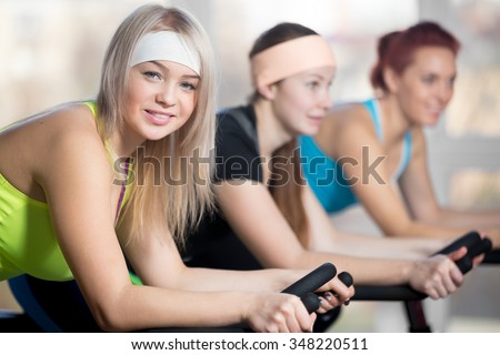 Fitness practice, group of three fit beautiful cheerful females cycling in sports club, doing cardio exercises for slimming, warming up during sport lesson in class, focus on smiling blond woman - stock photo