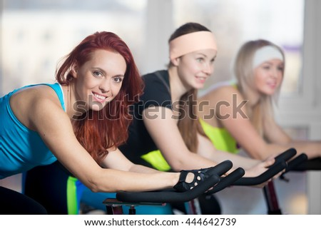 Fitness practice, group of three fit beautiful cheerful females cycling in sports club, warming up during sport lesson in class, focus on friendly smiling young woman in blue tank top