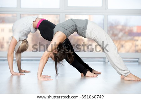 Fitness practice, group of two beautiful fit young people working out in sports club, doing stretching workout, bridge exercise, urdhva dhanurasana, Upward Bow (Wheel) yoga Pose in class - stock photo