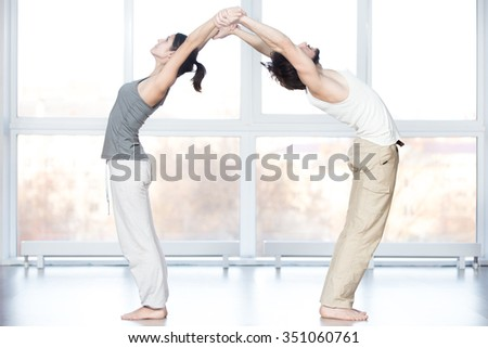 Fitness practice, group of two beautiful fit young people working out in sports club, doing stretching exercises together in class, Standing Backward Bend posture, Ardha Chakrasana, Half Wheel pose - stock photo