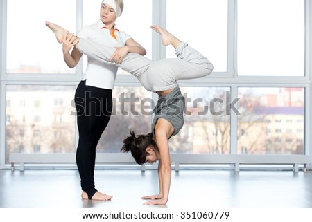 Fitness practice, instructor helping young beautiful student female to do handstand pose with bent legs in class, two fit people working out together in sports club, full length - stock photo