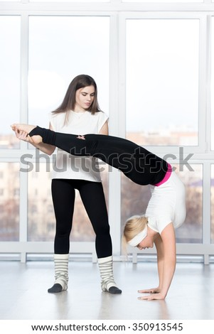Fitness practice, partner helping young beautiful student female to do handstand with backbend in class, two fit people working out in sports club, full length