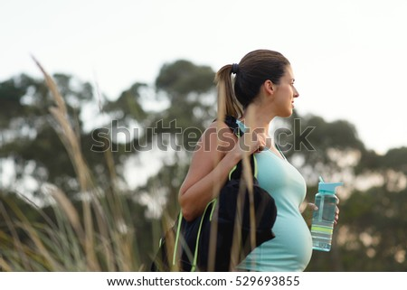 Fitness pregnant woman drinking water after outdoor workout. Healthy and active pregnancy lifestyle concept.