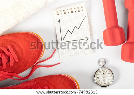 fitness progress. top view of notes, towel, red sneakers, barbells and stopwatch - stock photo