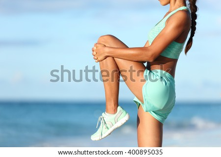 Fitness runner body closeup doing warm-up routine on beach before running, stretching leg muscles with standing single knee to chest stretch. Female athlete preparing legs for cardio workout. - stock photo