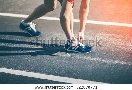 Fitness Runner man tying his sport shoes on a running track in the morning. Shoelaces, Urban jogger
