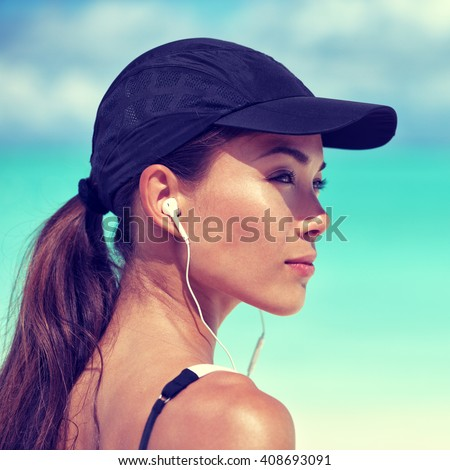 Fitness runner woman listening to music on beach. Portrait of beautiful girl wearing earphones earbuds and running cap for sun protection. Asian woman healthy and active in summer.  - stock photo