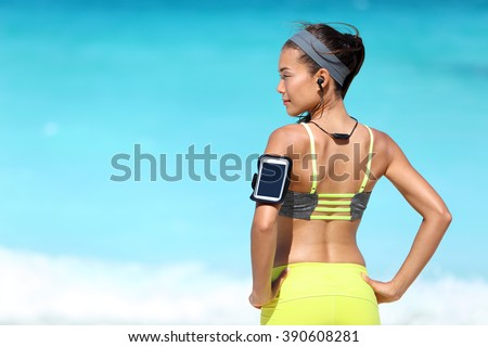 Fitness runner woman with fit back wearing phone armband and wireless headphones on ocean background. Multiracial exercise girl jogging on summer beach with sports smartphone touchscreen for app. - stock photo