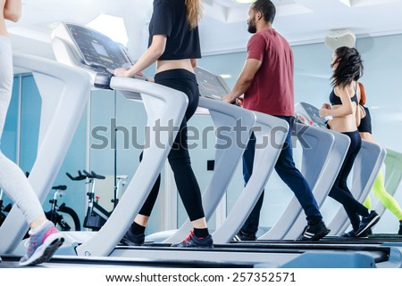 Fitness running people. Sports people running on the treadmill at the gym. Athletes wearing sportswear and running in the gym a rear view athletes. - stock photo