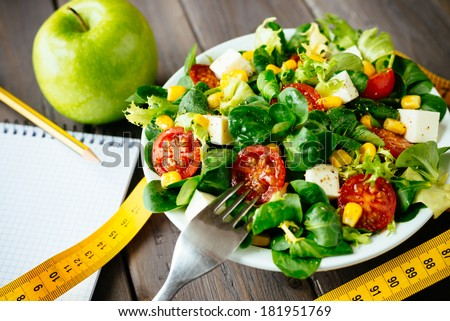 Fitness salad and measuring tape on rustic wooden table. Mixed greens, tomatos, diet cheese, olive oil and spices for healthy lifestyle concept. - stock photo