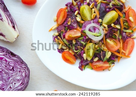 Fitness salad with purple cabbage,cherry tomatoes,cucumbers,cedar wood nuts,and carrots, - stock photo