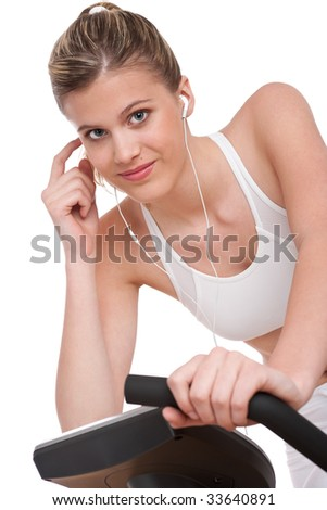 Fitness series - Woman with headphones cycling on white background - stock photo