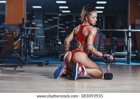 Fitness sexy athletics muscled woman in red sport clothing posing sitting on floor in gym - stock photo
