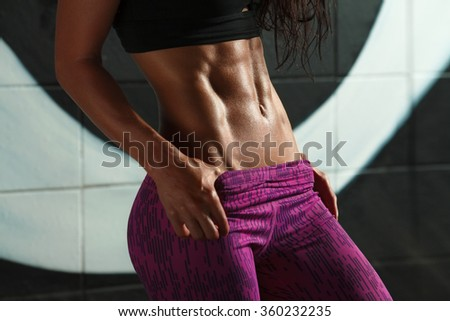Fitness sexy woman showing abs and flat belly. Beautiful muscular girl, shaped abdominal, slim waist - stock photo