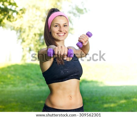 Fitness Slim Woman Training with dumbbells. Smiling attractive female practicing using hand weights outdoor. Healthy lifestyle workout concept on beautiful summer day. - stock photo