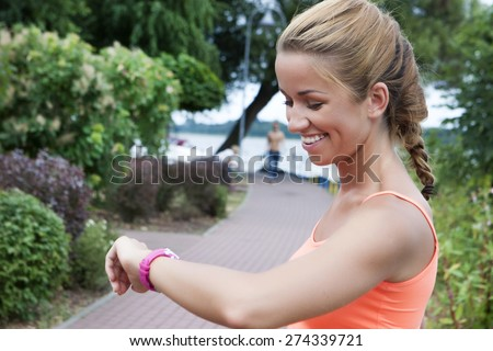 fitness smiling woman looking at heart rate monitor on hand