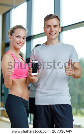 fitness, sport, advertising, technology and diet concept - smiling young woman and personal trainer with smartphone in gym showing thumbs up - stock photo