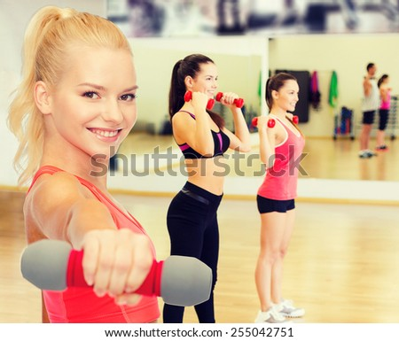 fitness, sport and diet concept - smiling beautiful sporty woman with dumbbell - stock photo