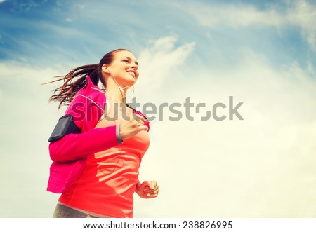 fitness, sport and lifestyle concept - smiling young woman with earphones running outdoors - stock photo