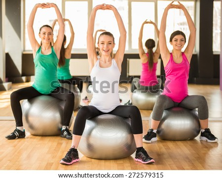 Fitness, sport and lifestyle concept - three pregnant women with exercise balls in gym. - stock photo