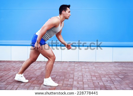 Fitness, sport and people concept - lifestyle photo man running in the city against colorful wall - stock photo